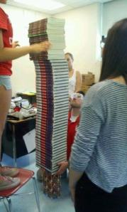 Students use textbooks and notebooks to demonstrate how much weight their tower can withstand.